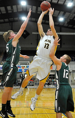 Alva's Riley Hess shoots between Thomas defenders, Trent Dunaway and Tyler Mannering during the class 2A area tournament Saturday at the Chisholm Trail Expo Center. (Staff Photo by BILLY HEFTON)