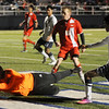 Del City goalie,  Joshua Hart (left), stops a kick on goal by Enid's Yancarlos Duenas during the Plainsmen's homecoming game at D. Bruce Selby Stadium Friday, March 8, 2013. (Staff Photo by BONNIE VCULEK)