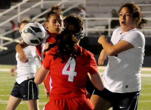 Enid's Claudia Huerta kicks the ball between two Del City defenders near the goal line during the Pacers' 9-0 win at D. Bruce Selby Stadium Friday, March 8, 2013. (Staff Photo by BONNIE VCULEK)