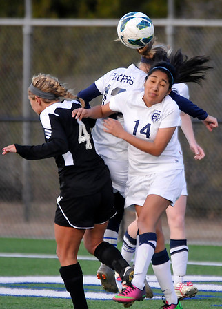 Enid's Jessica Ramirez and Kaitlin Bell heads the ball away from a a Tulsa Union player Tuesday at D. Bruce Selby Stadium. (Staff Photo by BILLY HEFTON)