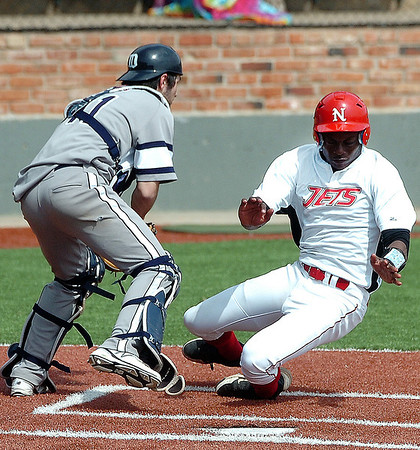 NOC Enid's Nik Gifford avoids DMACC's Anthony Mrosla to score Saturday during the first game of a doublehitter at David Allen Memorial Ballpark. (Staff Photo by BILLY HEFTON)