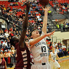 Pond Creek Hunter's Zach Rayner puts up a shot from under the basket agianst Malic Johnson of Hollis during the first round of the state basketball tournament Thursday at the Yukon High School. (Staff Photo by BILLY HEFTON)