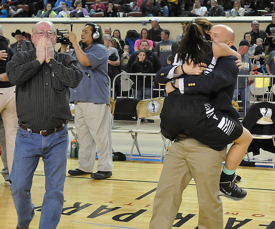 Pond Creek-Hunter Jade Jones jumps into her father's arms, Darin Jones, after the Lady Panthers defeated Seiling Saturday at the State Fair Arena in Oklahoma Cityas R.D. Schuermann (left) celebrates. (Staff Photo by BILLY HEFTON)