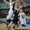 Pond Creek Hunter's Jade Jones goes under Cheyenne/Reydon's Kate Sander for a basket in a class A state semi-final Friday at the State Fair Arena in Oklahoma City. (Staff Photo by BILLY HEFTON)