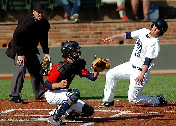 Enid's Bobby Russell slides in behind OKC Bronco catcher, Jake Johnson, to score Tuesday at David Allen Memorial Ballpark. (Staff Photo by BILLY HEFTON)