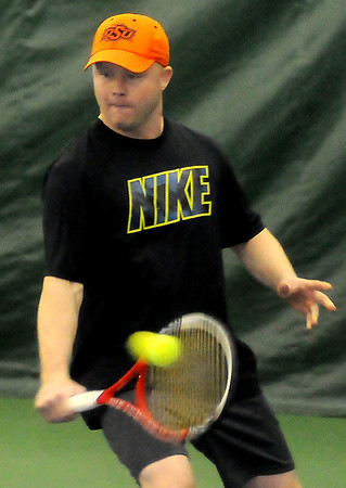 Nick Wolf, with the Enid Tennis Association, hits a return during the Larry McClure-Edward Jones Tennis Cup mixed-doubles competition at Oakwood Country Club Saturday, March 8, 2014. (Staff Photo by BONNIE VCULEK)