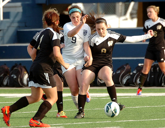 Enid's Sophie Holle runs through Woodward defenders to get to the ball Tuesday at D. Bruce Selby Stadium. (Staff Photo by BILLY HEFTON)