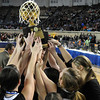 Members of the Pond Creek-Hunter Lady Pathers raise the state championship trophy after defeating Seiling Saturday at the State Fair Arena in Oklahoma City. (Staff Photo by BILLY HEFTON)