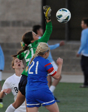 Enid goalkeeper, Grace Enmeier knocks the ball awzy from Bixby's Madeline Muellar Friday at D. Bruce Selby Stadium. (Staff Photo by BILLY HEFTON)
