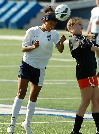 Enid's Abigail Resendiz heads the ball away a Tulsa Washington defender Tuesday at D. Bruce Selby Stadium. (Staff Photo by BILLY HEFTON)