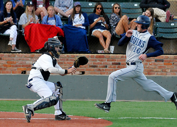 Enid's Kros Bay waits on the ball as Bartlesville's Josh Louthan scores Monday at David Allen Memorial Ballpark. (Staff Photo by BILLY HEFTON)