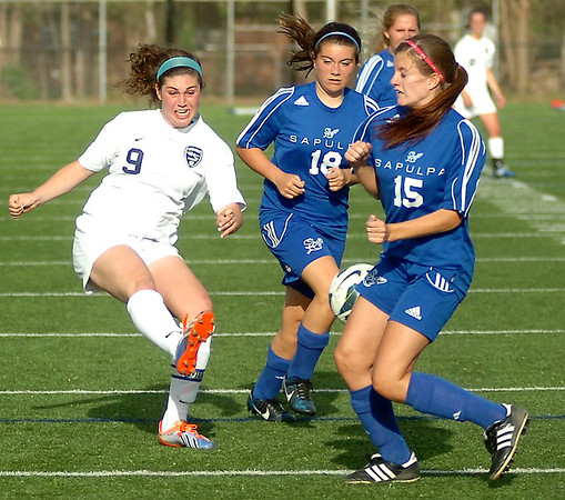 Enid's Sophie Holle takes a shot on goal between two Sapulpa defenders during the Pacers' 3-0 win on Senior Night at D. Bruce Selby Stadium Friday, April 25, 2014. (Staff Photo by BONNIE VCULEK)