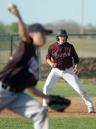 Pioneer's Kamen Lounsbury (right) takes a lead off first as Frontier's P.J. Burnett delivers a pitch during the Class A District winner's bracket game at John D. Riesen Field Thursday, April 24, 2014. (Staff Photo by BONNIE VCULEK)