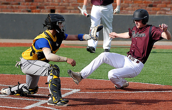 Pioneer's Blake Gabriel slides into home ahead of the tag from Drummond's Anthony Foley Saturday during the third place game of the Merrifield Office Plus Invitational. (Staff Photo by BILLY HEFTON)