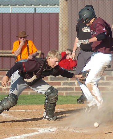 Pioneer's Kade Cronkhite knocks the ball from the glove of Frontier's Tristan Harris as Cronkhite scores for the Mustangs in the top of the second inning during the Class A District baseball winner's bracket game at John D. Riesen Field Thursday, April 24, 2014. (Staff Photo by BONNIE VCULEK)