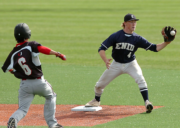 Enid's Tanner Fore catches a throw to force out Tulsa Union's Pedro Varela Saturday at David Allen Memorial Ballpark. (Staff Photo by BILLY HEFTON)