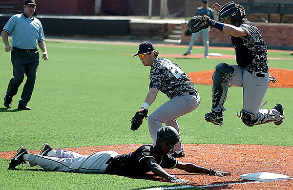Midwest City's Anthony Barclay dives to third ahead of the tag by Enid's Braden Rogers as catcher, Kros Bay, leaps over the play Friday at David Allen Memorial Ballpark. (Staff Photo by BILLY HEFTON)