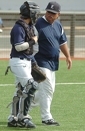 Coach Bill Mayberry talks to Kros Bay as they walk to the mound Saturday against Tulsa Union. (Staff Photo by BILLY HEFTON)