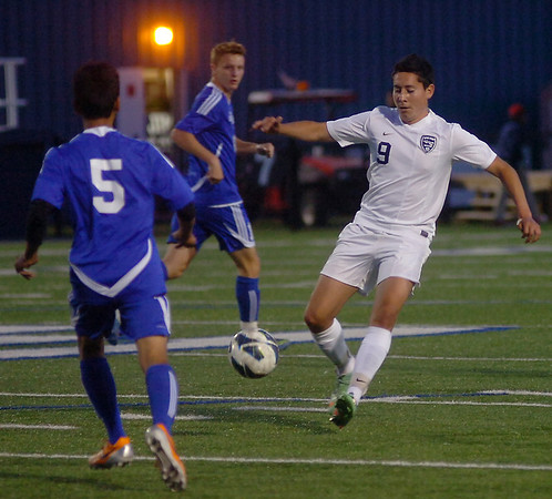Enid's Armando Gutierrez steals the ball from two Sapulpa players during Senior Night at D. Bruce Selby Stadium Friday, April 25, 2014. (Staff Photo by BONNIE VCULEK)