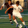 Enid's Justin Miles gets by a Tulsa Washington defender Tuesday at D. Bruce Selby Stadium. (Staff Photo by BILLY HEFTON)