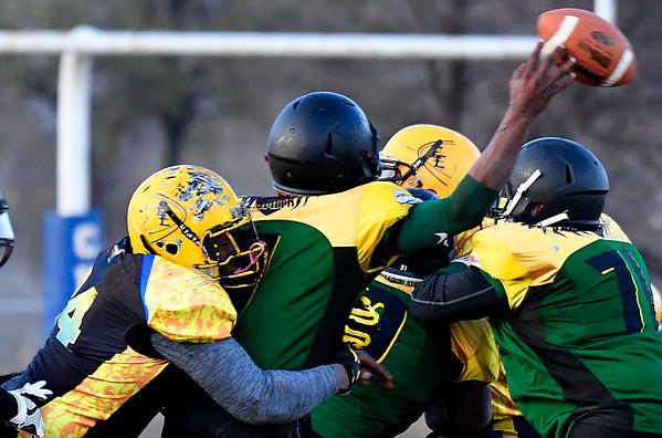 Enid Enforcers' Lantz Mathers hits Arkansas quarterback, Sam Cole, Saturday March 11, 2017 at Waukomis High School. (Billy Hefton / Enid News & Eagle)