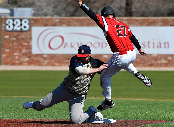 NOC Enid's Matt Conerly tries to avoid the tag of Northland's Blake Fetting Friday March 3, 2017 at David Allen Ballpark. (Billy Hefton / Enid News & Eagle)