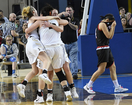 Seiling's Karly Gore, Raylee Tautfest and Macy Gore celebrate winning the class A state championship as Frontier's Shelby Black walks away Saturday March 3, 2018 at the State Fair Arena in Oklahoma City.  Tautfest finished with a game high 32 points. (Billy Hefton / Enid News & Eagle)