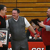 NOC Enid's head mens basketball coach, Greg Shamburg (center), hugs head weomen's coach, Scott Morris (left), as he is presented a plaque by athletic director, Jeremy Hise (right), during a pregame ceremony honoring him on his last home game Thursday March 1, 2018 at the NOC Mabee Center. (Billy Hefton / Enid News & Eagle)