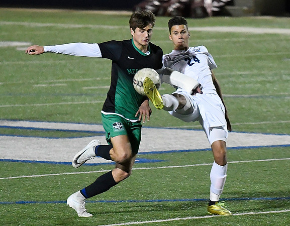 Enid's Nick Coker kicks the ball away from Bishop McGuinness' Andrew Wisniewski Tuesday March 13, 2018 at D. Bruce Selby Stadium. (Billy Hefton / Enid News & Eagle)