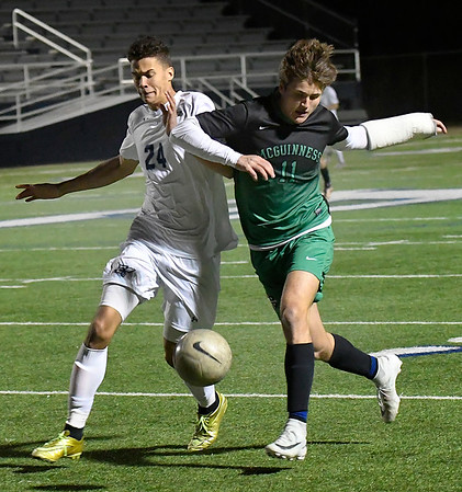 Enid's Nick Coker and Bishop McGuinness' Andrew Wisniewski tussel for the ball Tuesday March 13, 2018 at D. Bruce Selby Stadium. (Billy Hefton / Enid News & Eagle)