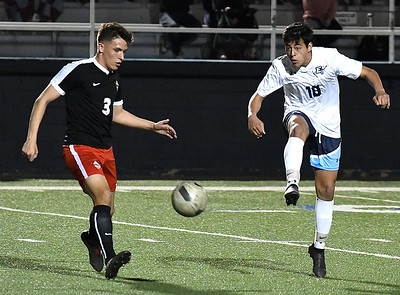 Enid's Ivan Delgadillo knocks the ball upfield against Mustang's Hayden Ray Thursday March 15, 2018 at D. Bruce Selby Stadium. (Billy Hefton / Enid News & Eagle)