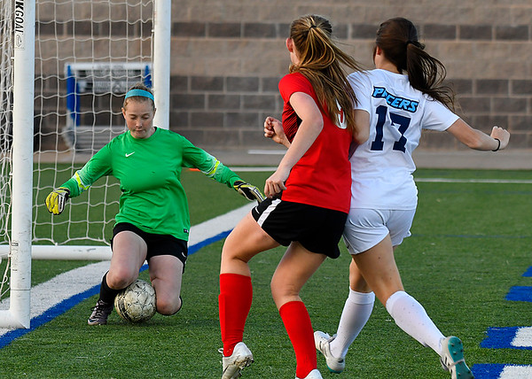 Enid goalie, Katie Goodpasture, stops a shot of Mustang's Gracie Cornelius as Mashell Kent defends Thursday March 15, 2018 at D. Bruce Selby Stadium. (Billy Hefton / Enid News & Eagle)