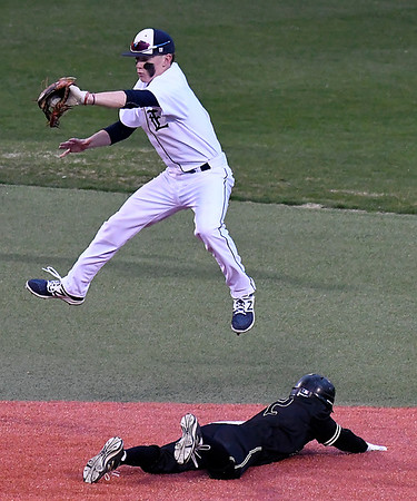 Enid's Ambren Voitik leaps to catch the ball as Broken Arrow Monday Jacob Simpson slides into second base March 26, 2018 at David Allen Memorial Ballpark. (Billy Hefton / Enid News & Eagle)