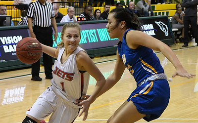 NOC Enid's Macie Jo Pierce drives to the basket against NEO's Raven Blackbear during the Region 2 championship game DSaturday March 9, 2019 at Oklahoma Baptist University in Shawnee. (Billy Hefton / Enid News & Eagle)