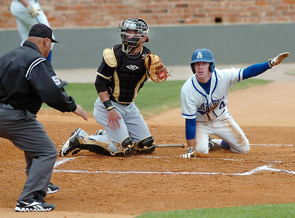 Tyler Cameron of Southern Arkansas signals safe with one arm as he and Harding catcher, Erin McCarver, wait for the umpire's call during the opening game of the Great American Conference tournament Saturday at David Allen Memorial Ballpark. (Staff Photo by BILLY HEFTON)
