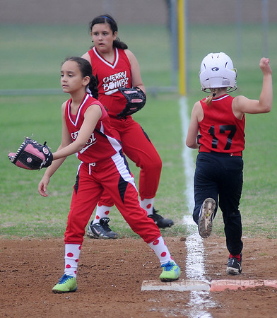 Heat's Allie Booth sprints past first as Cherry Bombz's Sierra Brown awaits the throw and Kalista Layton backs up the play during the Summer Smash 10-under Softball Tournament at Government Springs Park Saturday, May 17, 2013. (Staff Photo by BONNIE VCULEK)