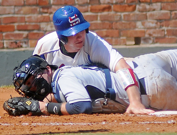 Murray State's Daniel Arthur reaches over Heartland Community College's Joe Gregory as he scores for the Aggies during the 75th annual NJCAA World Series Div II at David Allen Memorial Ballpark Thursday, May 30, 2013. Murray State won 6-0. (Staff Photo by BONNIE VCULEK)