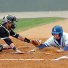 Tyler Cameron of Southern Arkansas beats the tag of Harding catcher, Erin McCarver, to score during the opening game of the Great American Conference tournament Saturday at David Allen Memorial Ballpark. (Staff Photo by BILLY HEFTON)