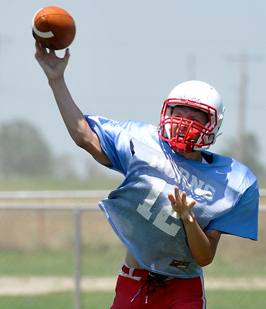Baily Cross throws a pass during spring football drills Monday at Chisholm High School. (Staff Photo by BILLY HEFTON)