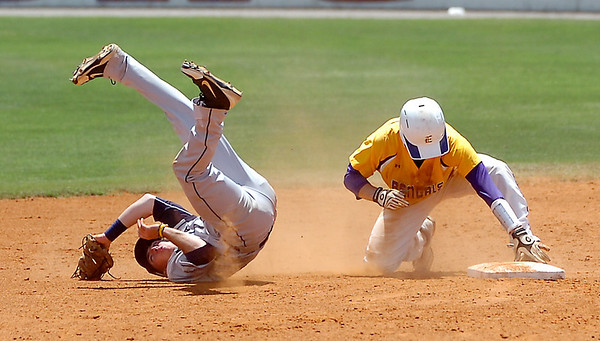 Heartland's Mason Snyder takes a tumble after coming down with a high throw  as LSU-Eunice's Derek Herrington slides into second during a winners bracket game Thursday in the NJCAA Div II World Series at David ALlen Ballpark. (Staff Photo by BILLY HEFTON)
