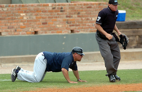 SWOSU head coach, Zack Saunders, goes low to get a better look at a close at third base against Harding Sunday during an elimination game in the Great American Conference tournament at David Allen Memorial Ballpark. (Staff Photo by BILLY HEFTON)