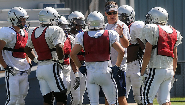 Enid's head football coach, Steve Chard, works with the Plainsmen defense during a spring practice at D. Bruce Selby Stadium Wednesday, May 22, 2013. (Staff Photo by BONNIE VCULEK)