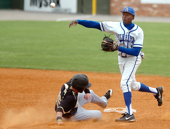 David Harris of Southern Arkansas throws to first after forcing out Erin McCarver during the opening game of the Great American Conference tournament Saturday at David Allen Memorial Ballpark. (Staff Photo by BILLY HEFTON)