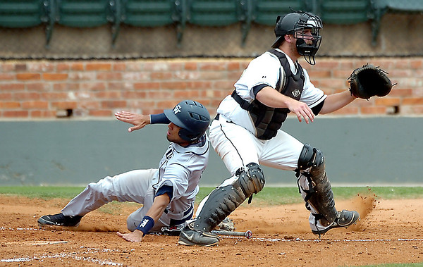 SWOSU's Brandon Ruiz slides around Harding catcher, Chris Hardey, to score Sunday during an elimination game in the Great American Conference tournament at David Allen Memorial Ballpark. (Staff Photo by BILLY HEFTON)