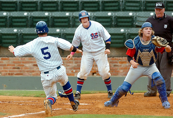 Murray State's Eddie Keiffer yells for teammate, Daniel Arthur (5), to slide at home plate has Avery Point catcher, Matt Harrison, waits on the ball during an elimination game Tuesday in the NJCAA Div II World Series at David Allen Ballpark. (Staff Photo by BILLY HEFTON)