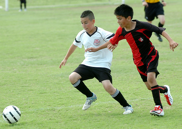 Geo Luperico of Red Star and Brandon Garcia of Atlas compete for the ball during the finals of the U-10 Enid Soccer Club Spring Recreational Tournament Sunday at the Enid Soccer Complex. (Staff Photo by BILLY HEFTON)