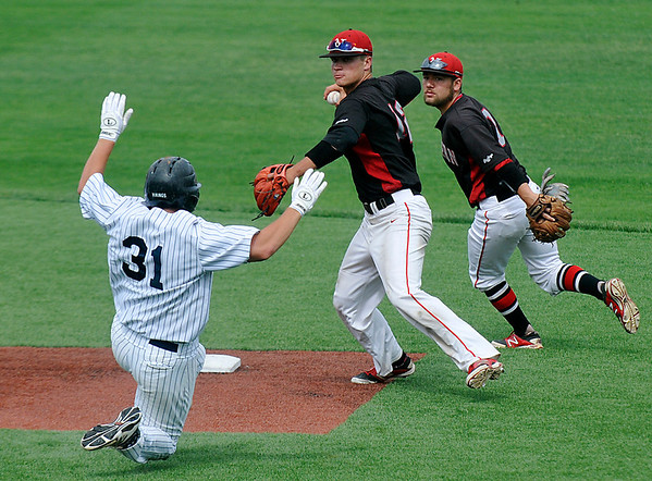 NOC Enid's Nik Yoning throws over Joe Boscia of Westchester CC after taking a toss from Dyce Applegate Sunday during a elimination game of the NJCAA DII World Series at David Allen Memorial Ballpark. (Staff Photo by BILLY HEFTON)