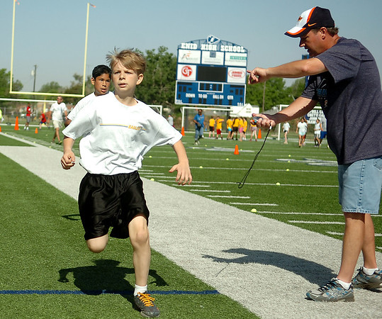 Brian Higbee, from Eisenhower Elementary School, wins the 800 meter run as Coach Steve Bloom checks Higbee's time during the Little Olympics competition at D. Bruce Selby Stadium Wednesday, May 7, 2014. (Staff Photo by BONNIE VCULEK)