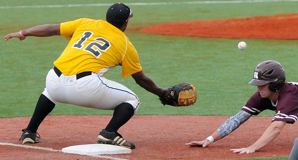 Hinds Community College's Toler Robinson (right) dives back to first as Pasco-Hernando State College's Joel Rosario awaits the throw during the NJCAA Division II World Series at David Allen Memorial Ballpark Tuesday, May 27, 2014. (Staff Photo by BONNIE VCULEK)