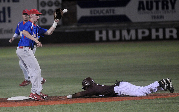 Hinds Commuity College's Quade Smith slides toward second as Lincoln Land Community College's Will Schneider makes the catch during the NJCAA Division II World Series at David Allen Memorial Ballpark in Enid, Okla. Saturday, May 24, 2014. (Staff Photo by BONNIE VCULEK)